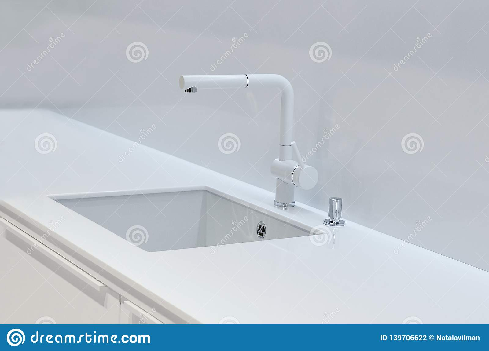 A new white kitchen sink made of artificial stone and a faucet. The concept of modern kitchen interior