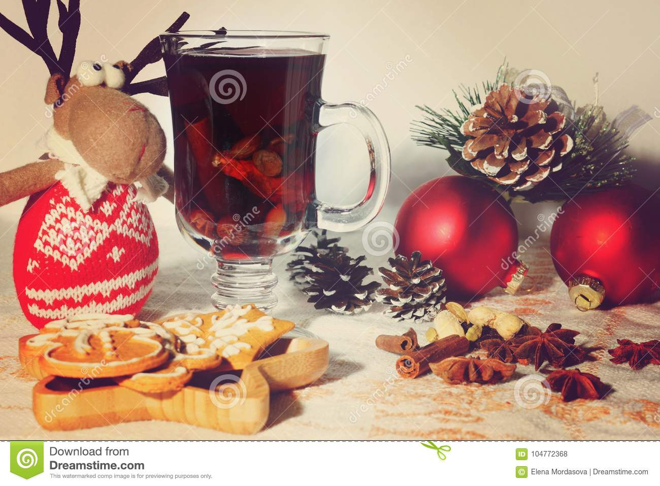 New Year celebratory table with mulled wine, ingredients and cookies, toy deer and Christmas decorations nearby