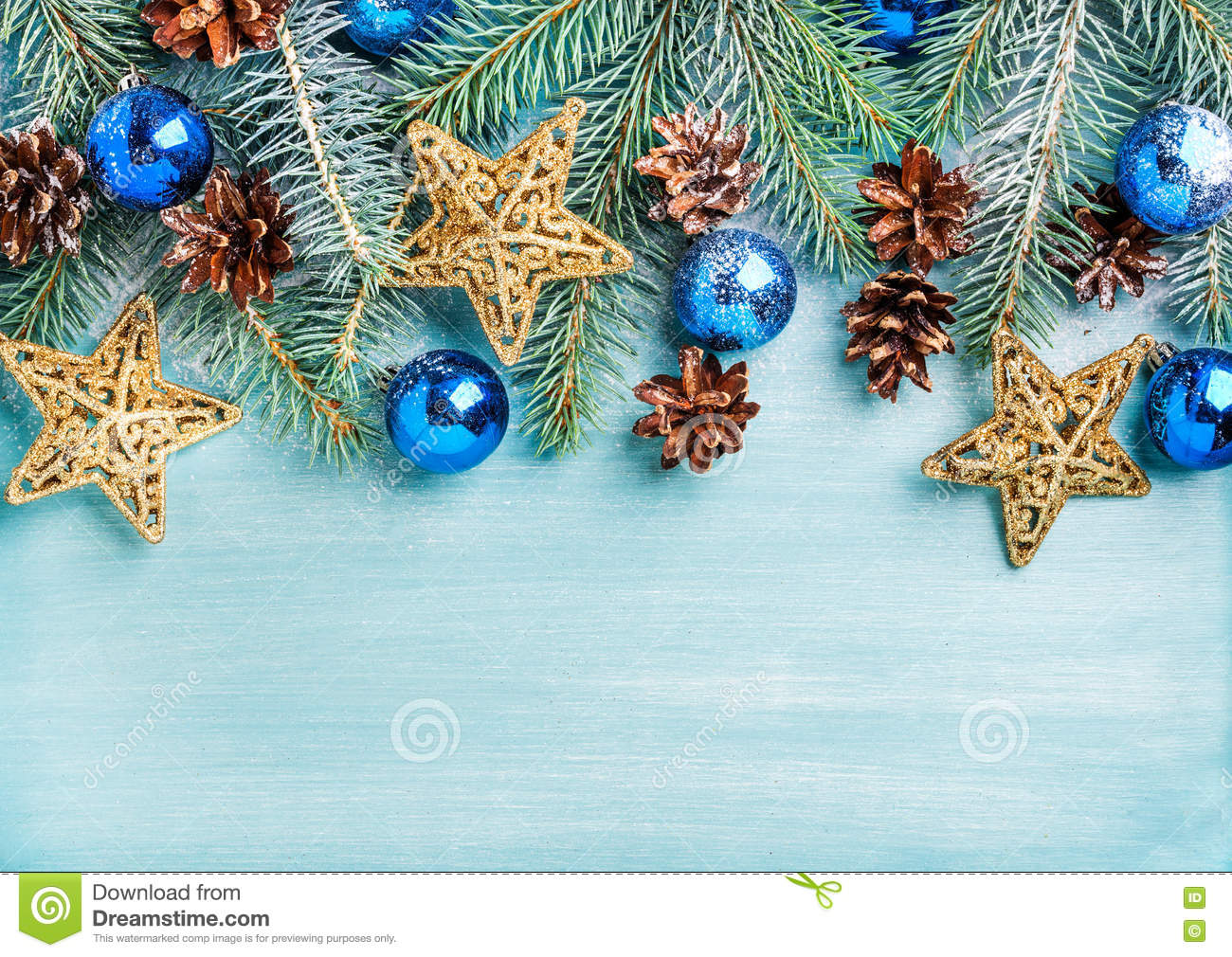 New Year or Christmas background: fir branches, blue glass balls, cones, golden stars over turquoise wooden backdrop