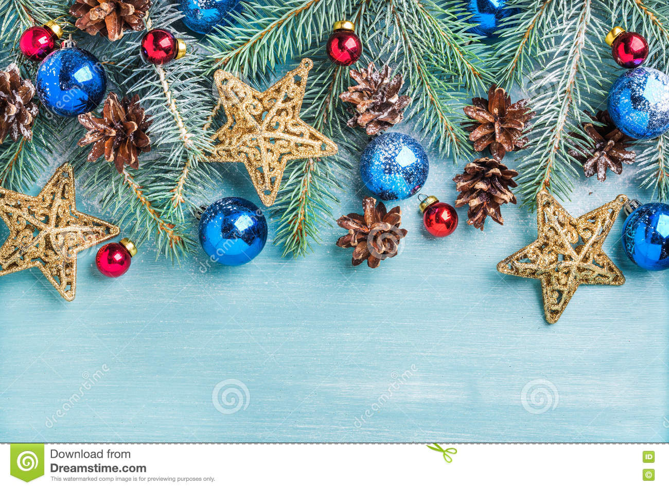 New Year or Christmas background: fir branches, colorful glass balls, cones and golden stars over blue painted wooden