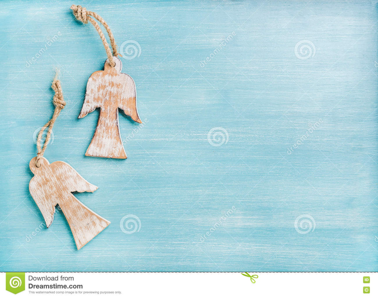 New Year or Christmas background: two wooden angels over blue painted backdrop, copy space