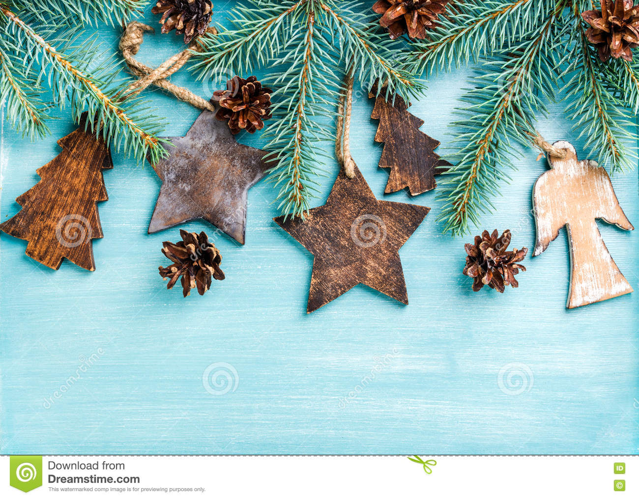 New Year or Christmas background: wooden angels, stars, small fir-trees, cones and branches over blue painted backdrop