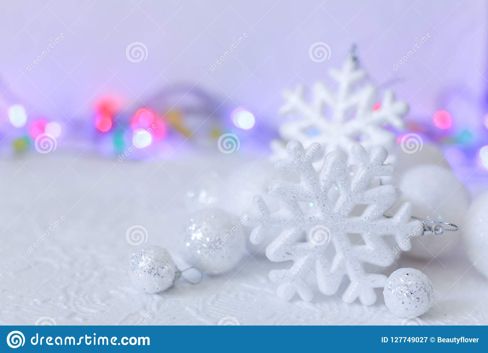 New year or Christmas decorations in silver and white colors with balls, snowflakes and garland bokeh