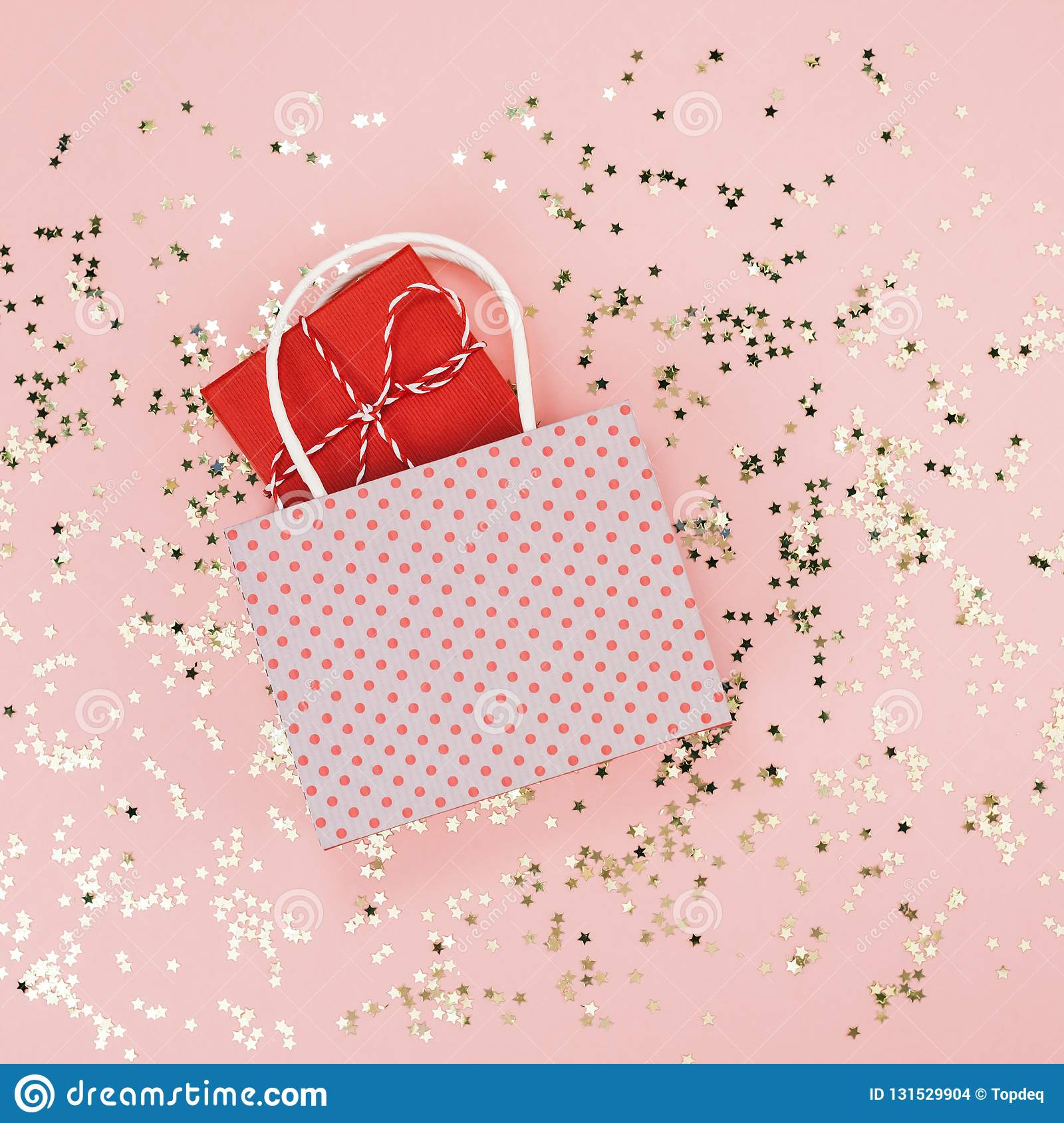 New Year Christmas sale Top view flat lay shopping bag with gift present golden stars confetti millennial pink background minimal
