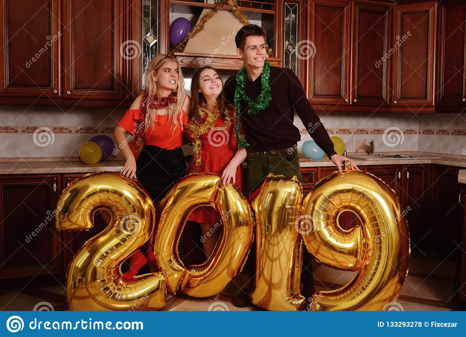 New 2019 Year is coming. Group of cheerful young people carrying gold colored numbers and have fun at the party