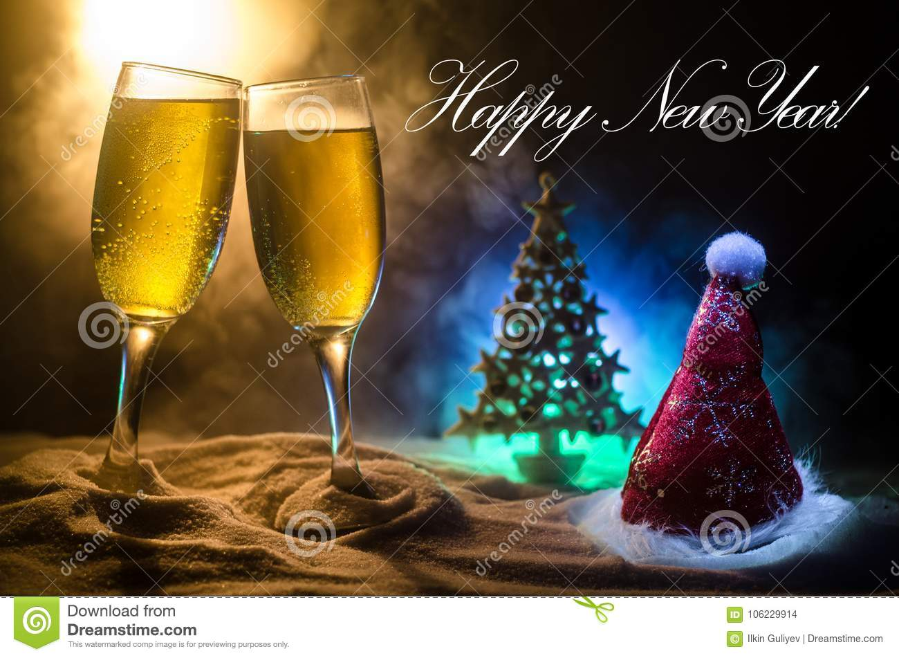 New Year Eve celebration background with pair of flutes and bottle of champagne with Christmas attributes (or elements) on snowy d