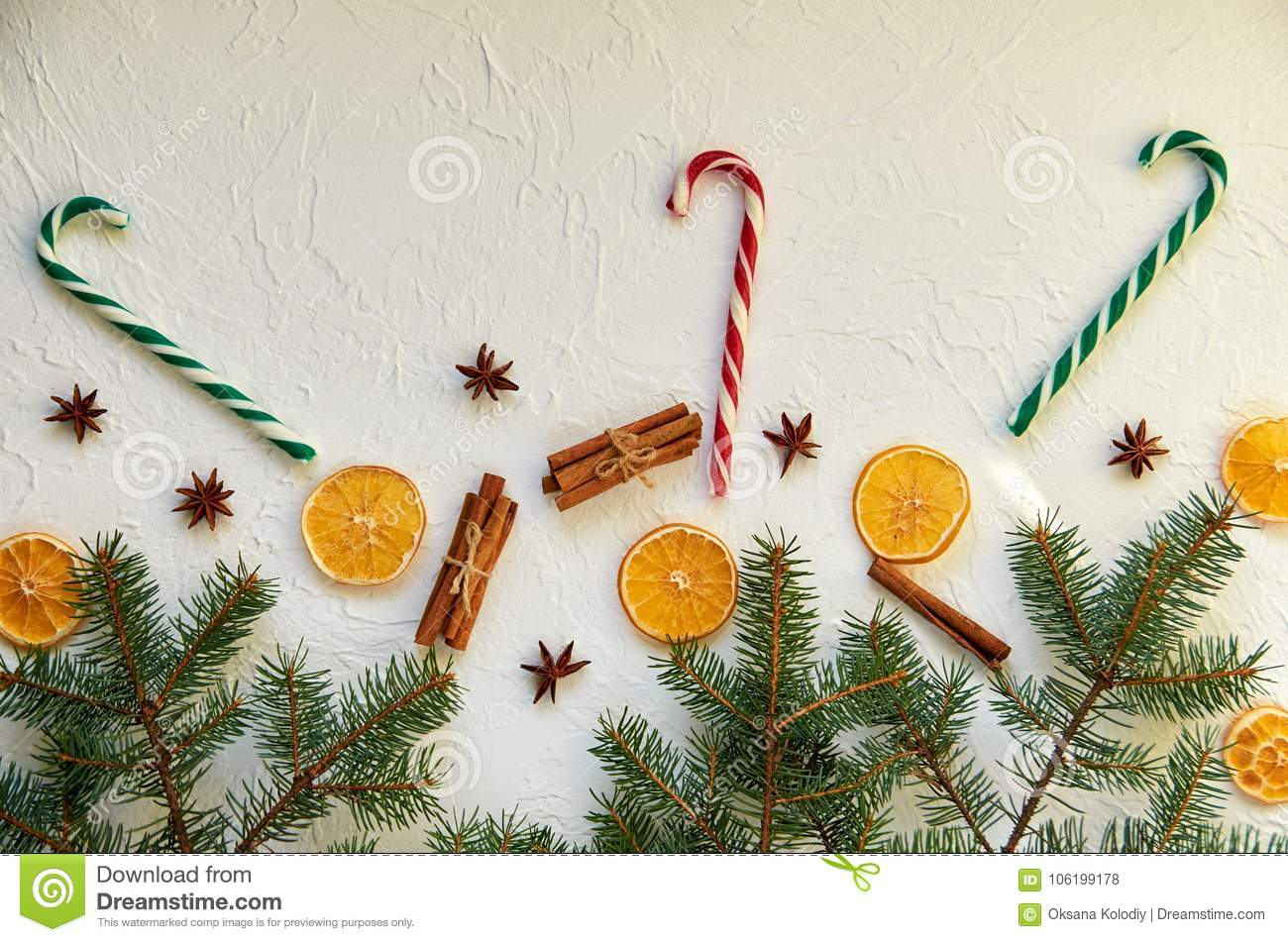 New year food decorations with fir branches, three red and green candy cones and traditional holiday spices: anise star, cinnamon