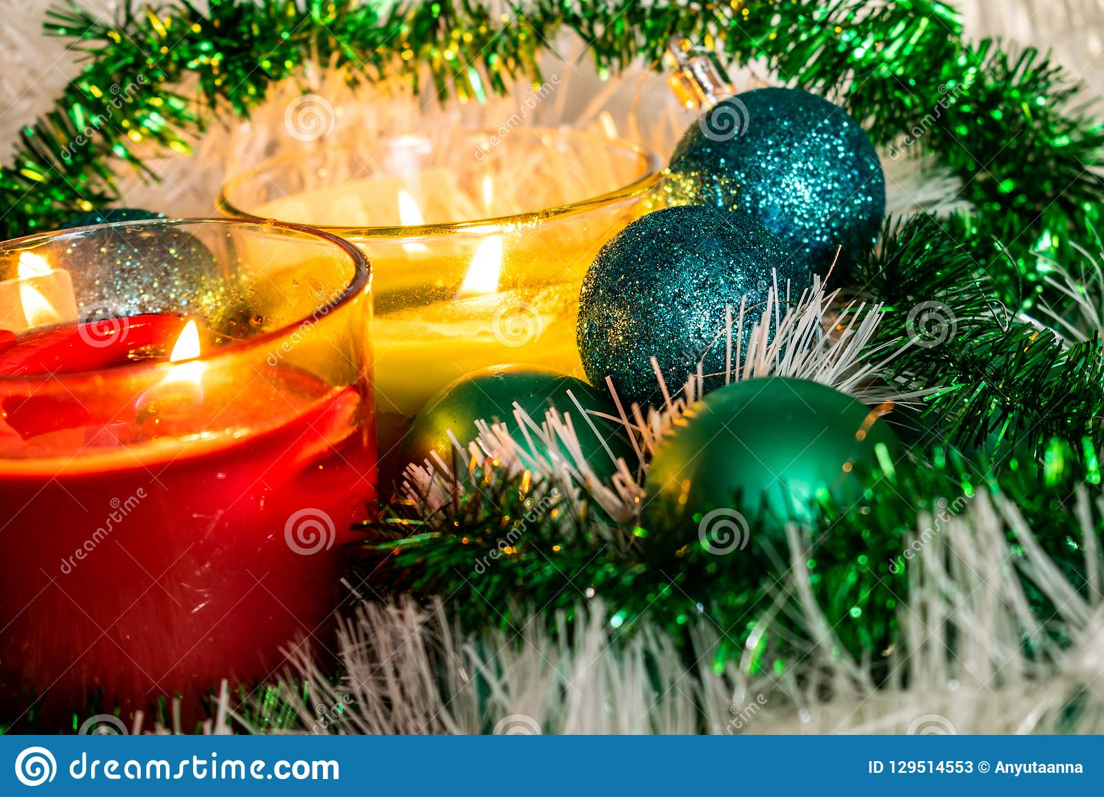 New year, green balls and decorations for the Christmas tree. Bright and beautiful scenery on a lemon background with white tinsel