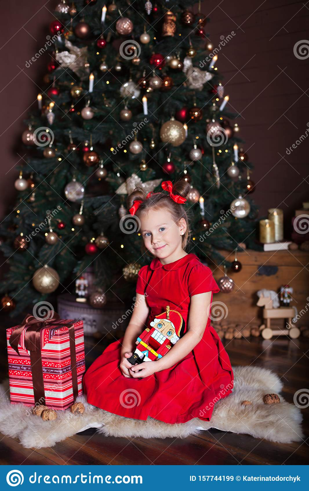 New Year 2020. Merry Christmas, happy holidays. Cute girl holds a nutcracker toy in hands in front of a Christmas tree and gifts.