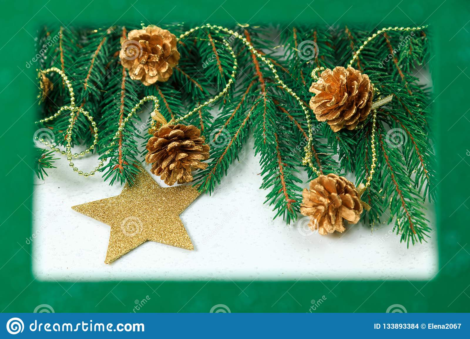Christmas background. Christmas jewelry on fir-tree branches, gold spheres, garlands in a green frame for a photo or an inscriptio