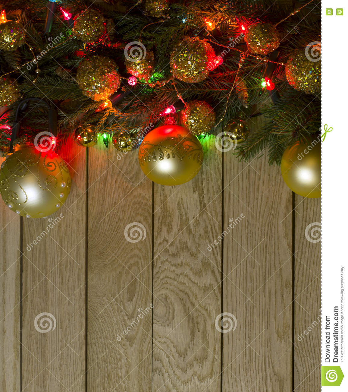 new years top border frame from christmas tree fir branches golden pine cones balls garland lights on vertical old wooden desk table background
