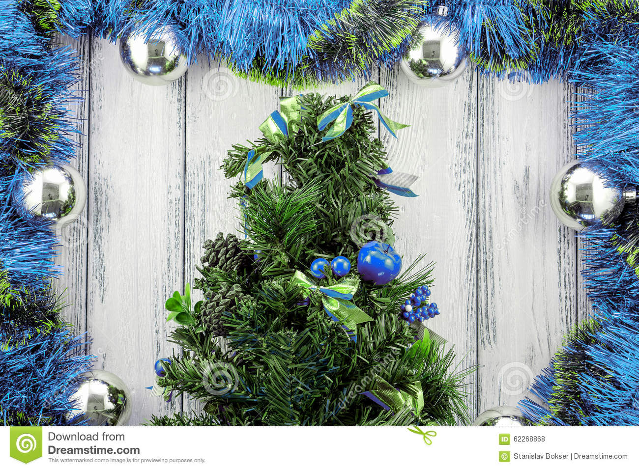 new year theme christmas tree with blue and green decoration and silver balls on white stylized wood background - Green Christmas Tree With Blue Decorations