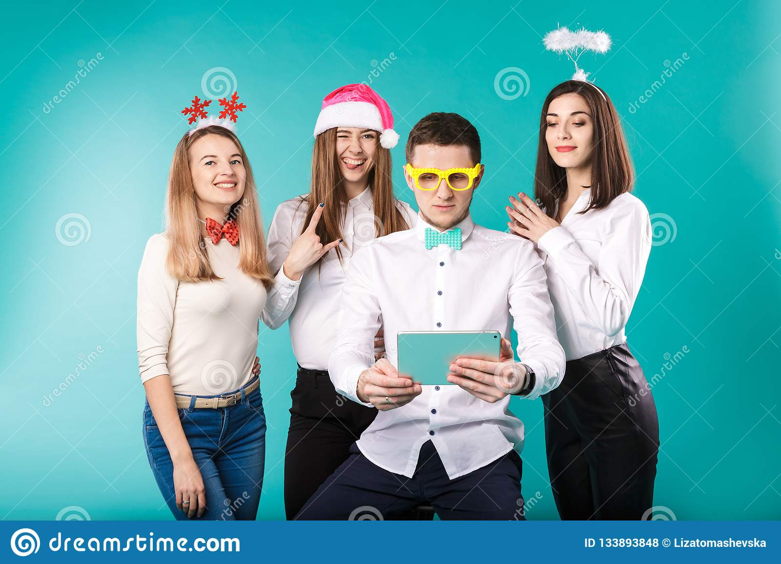 New Year theme Christmas winter office company employees. Group 4 young Caucasian people business smile holiday funny hats