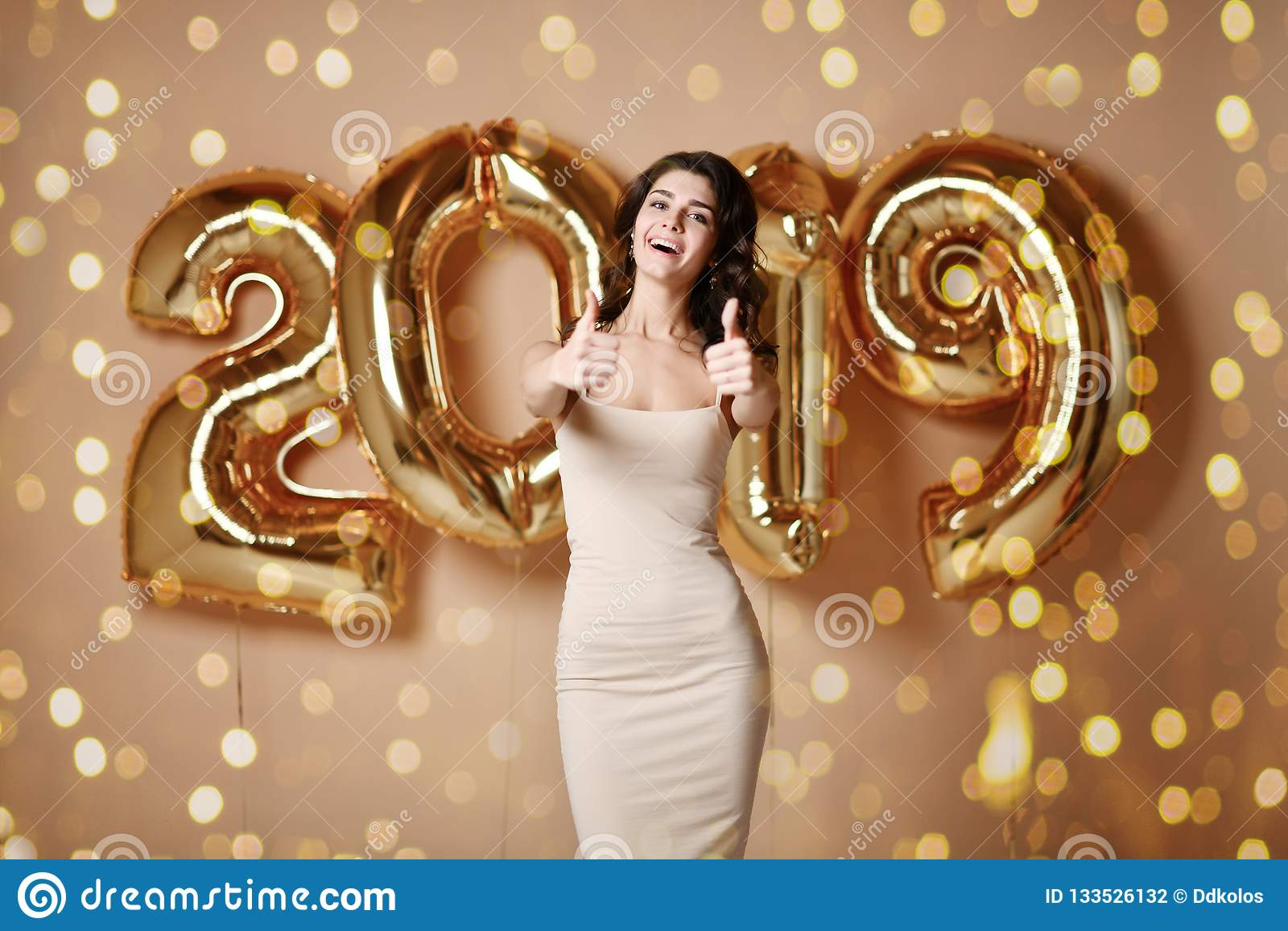 Portrait Of Beautiful Smiling Girl In Shiny Golden Dress Throwing Confetti, Having Fun With Gold 2019 Balloons On Background.
