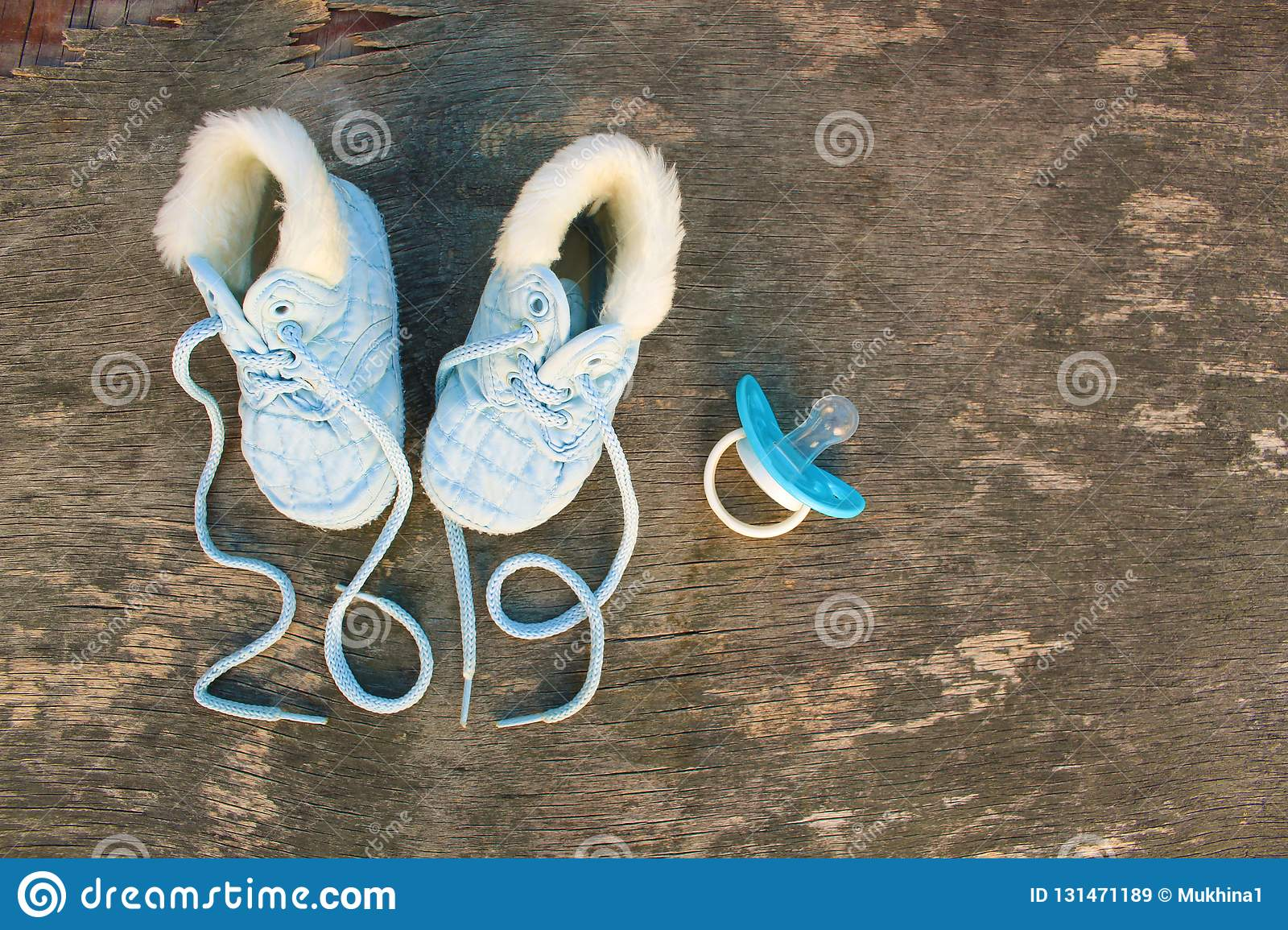 e068c9858ab3 2019 new year written laces of children`s shoes and pacifier on old wooden  background