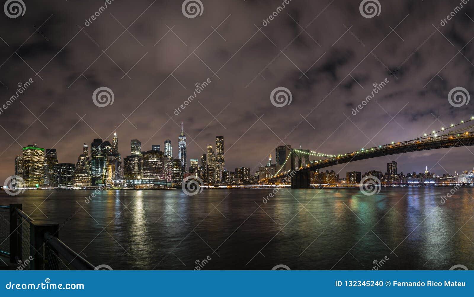 New York City Manhattan i stadens centrum panorama på natten med skyskrapor exponerade över East River