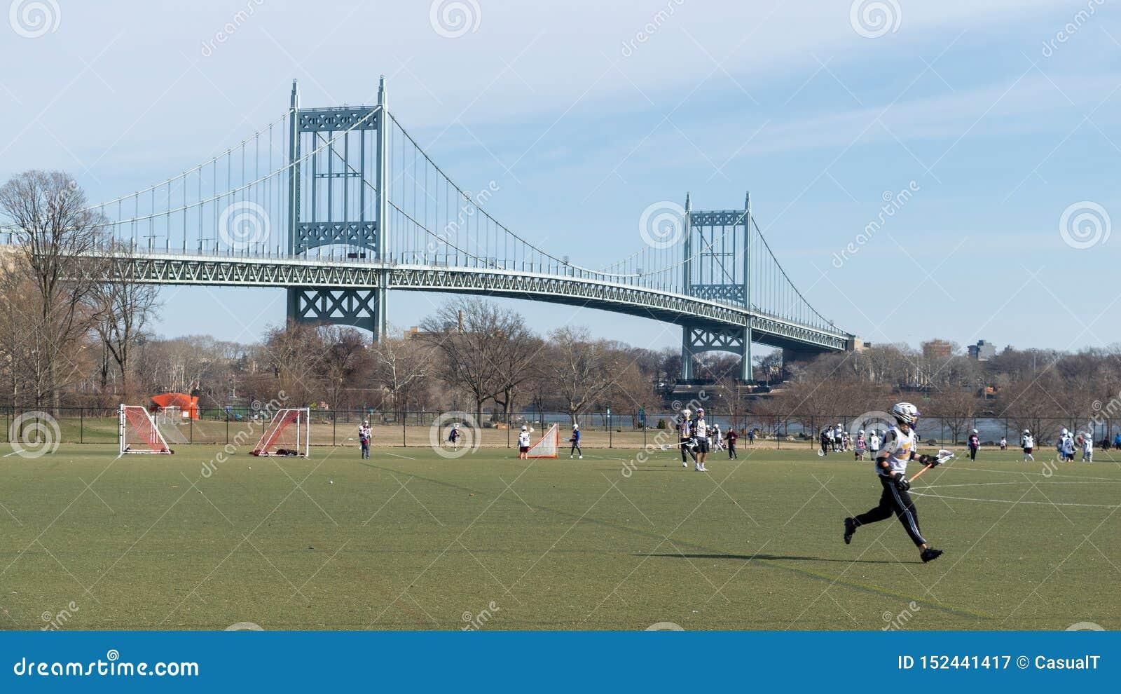 New York City, NY/USA - 3/19/2019: Equipe da lacrosse durante a prática na ilha de Randall, com a ponte de Triboro no
