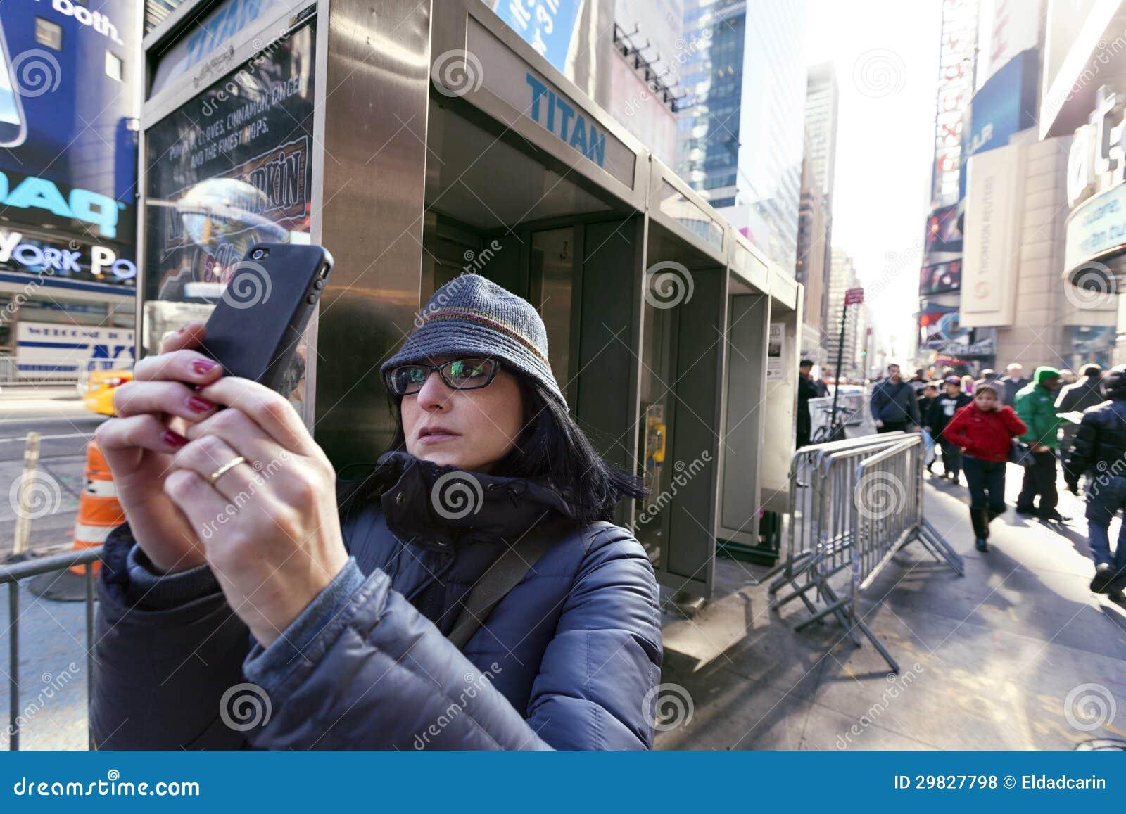 Vitória celular de Manhattan New York do Times Square do turista da fotografia