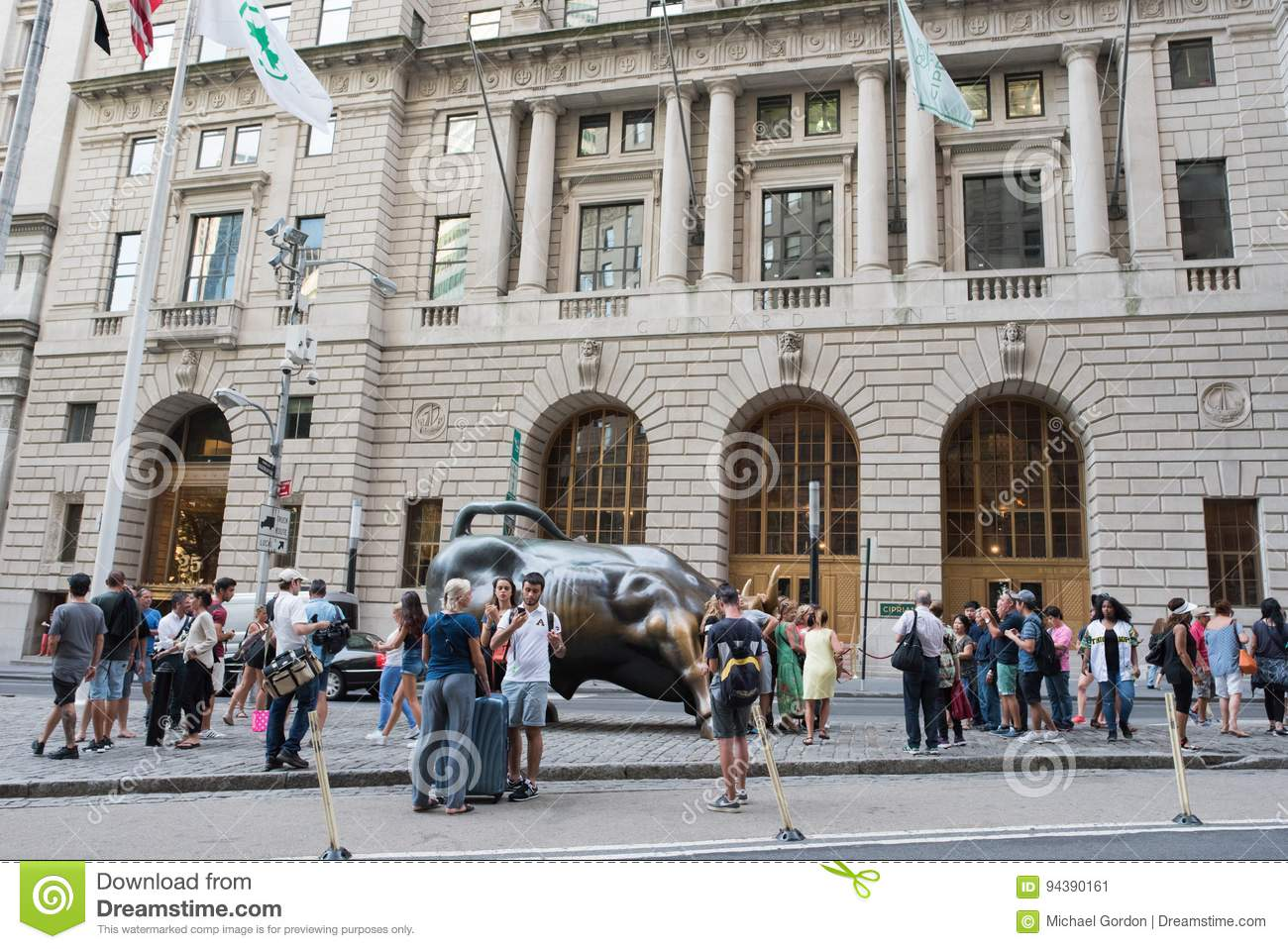 08103566 New York, NY: August 27, 2016: Tourists with `Charging Bull` sculpture.  `Charging Bull` was created as a form of guerilla art by Di Modica who  spent ...