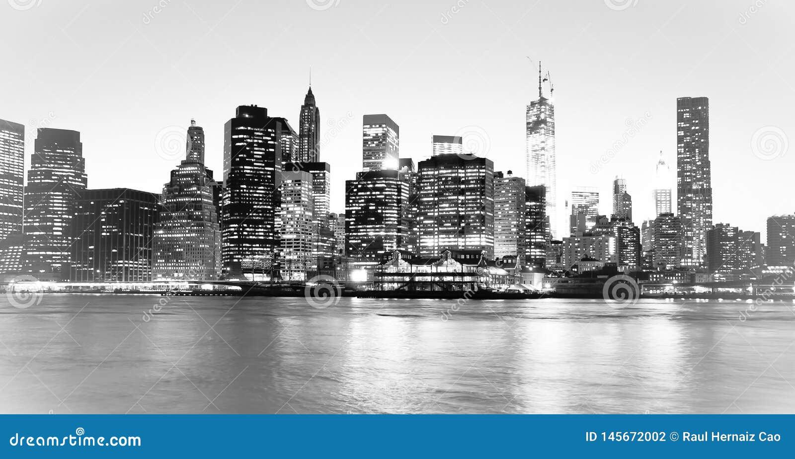 New York parkerar det finansiella området och Lower Manhattan på natten som beskådas från den Brooklyn bron H?g nyckel- svartvit