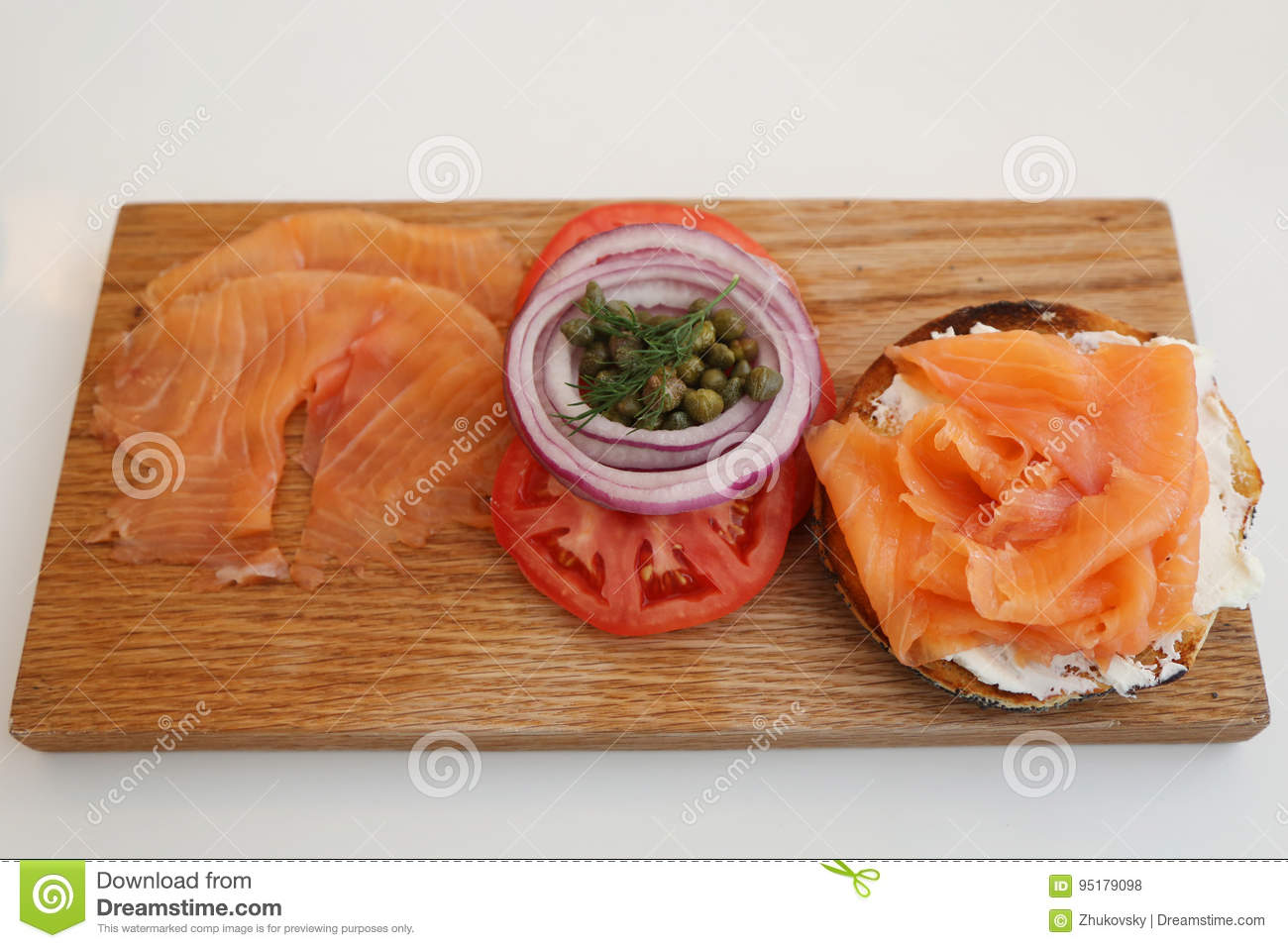 New York Style Bagel with smoked salmon on wooden board with cream cheese, tomato, onion and capers