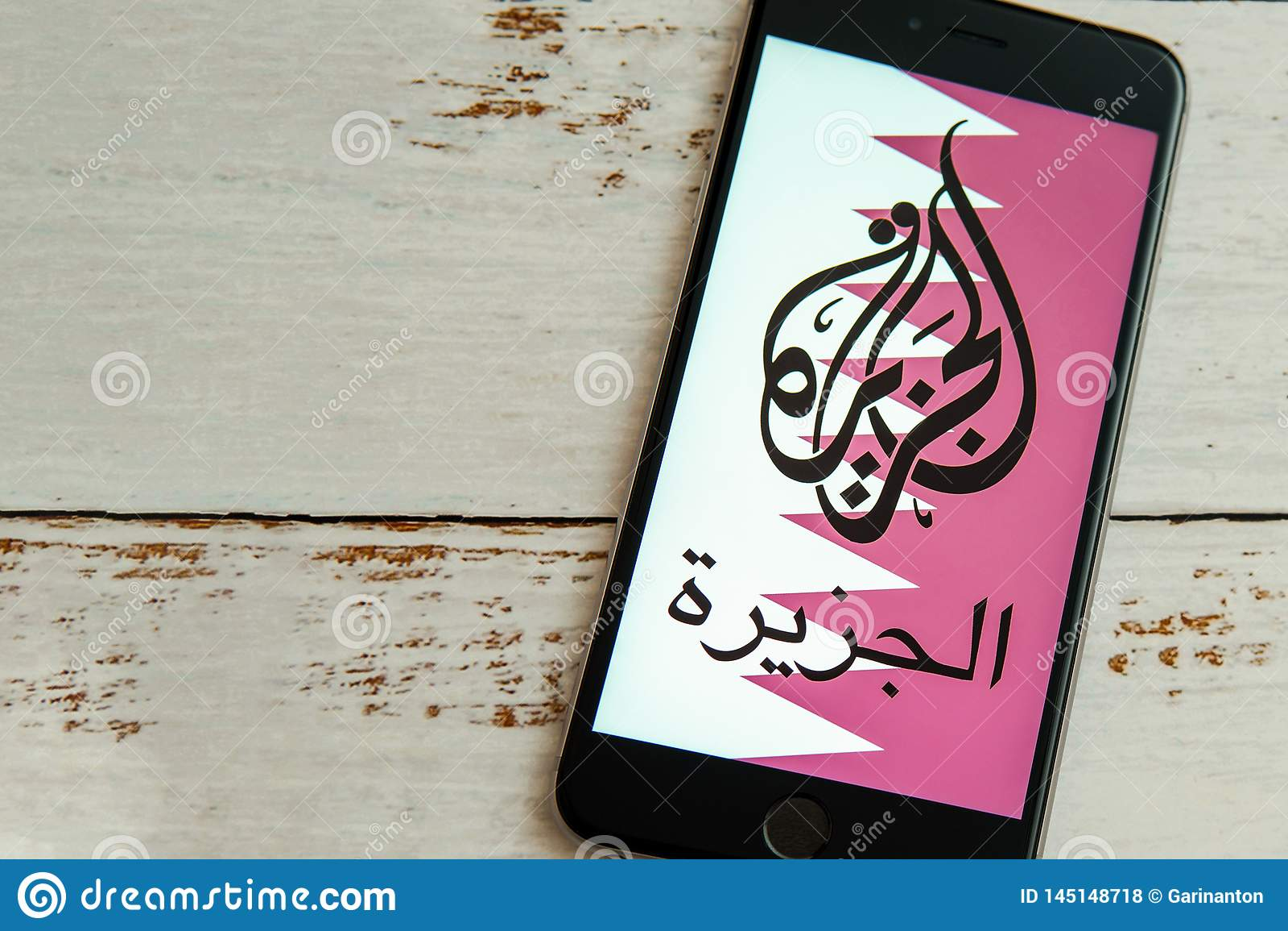 Black iPhone with logo of news media Al Jazeera on the screen.