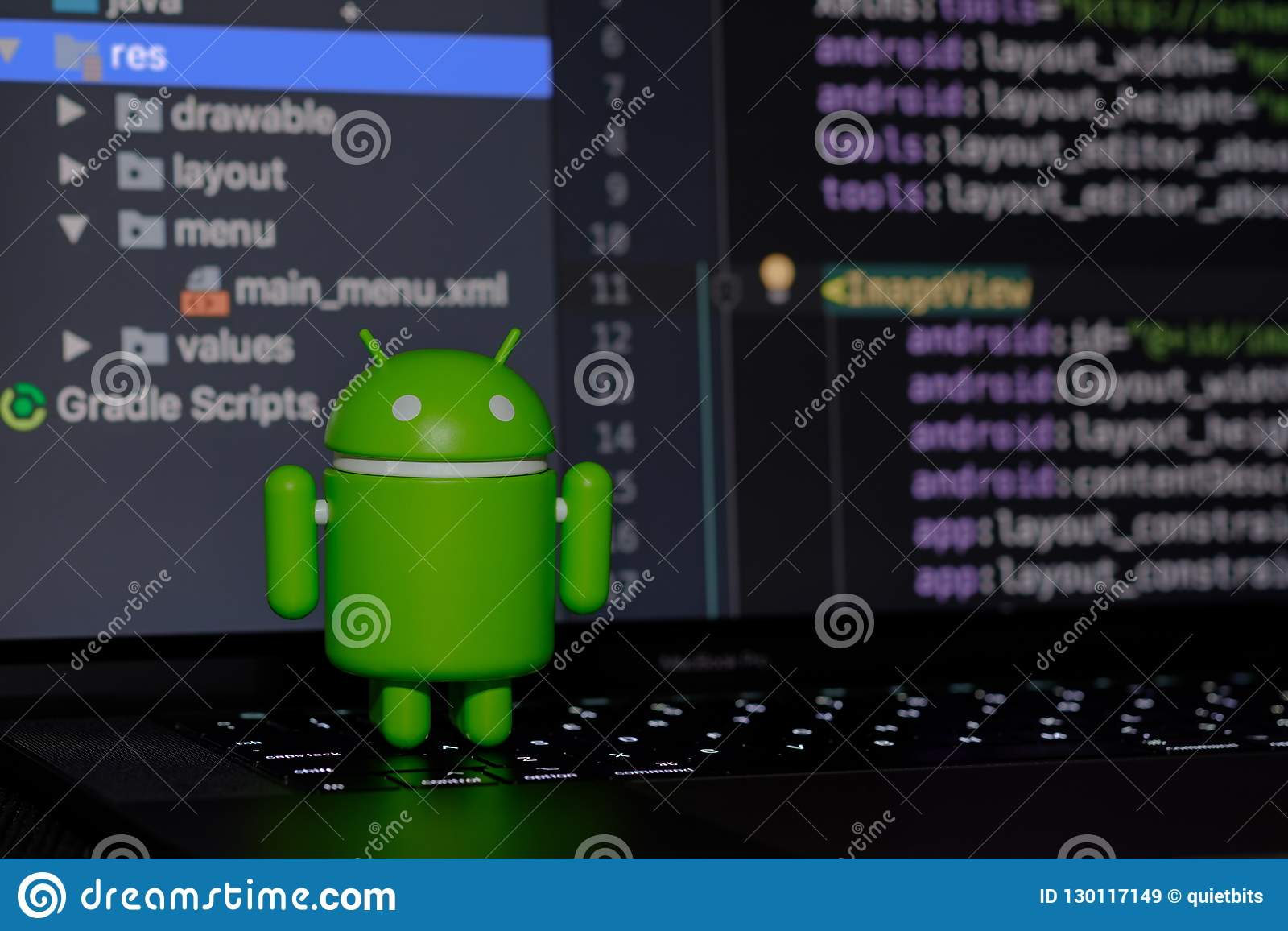 Google Android figure standing on laptop keyboard
