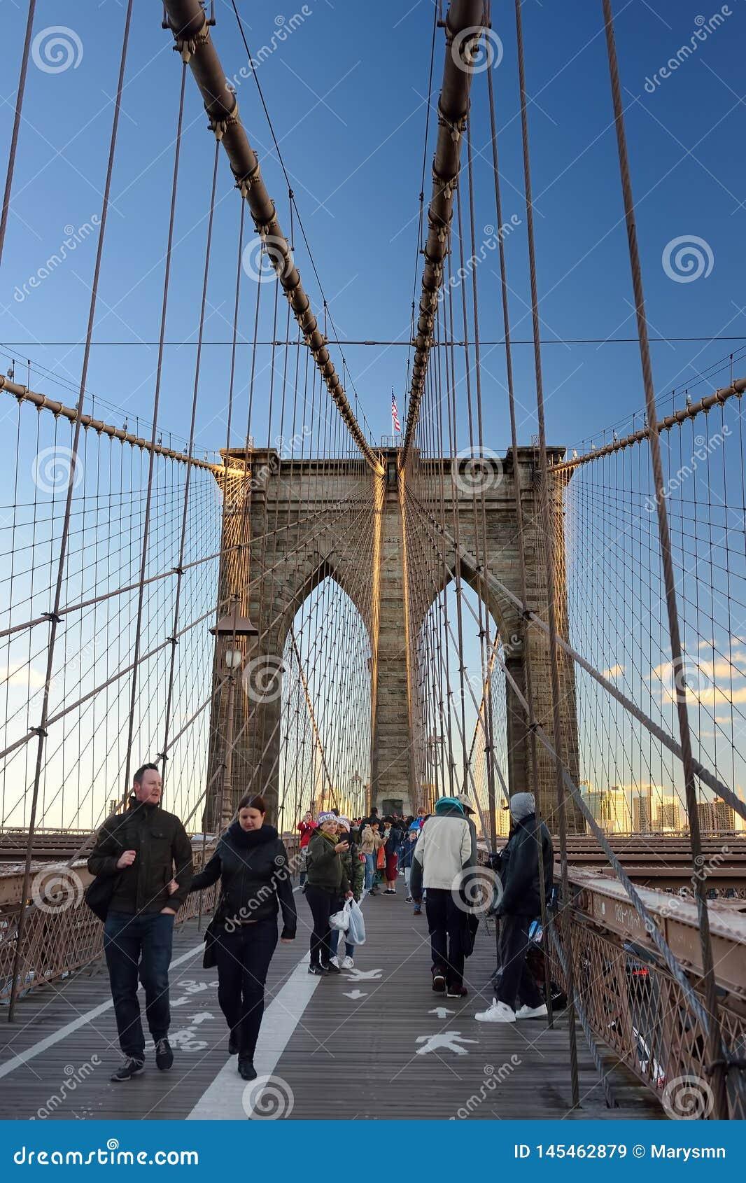 NEW YORK, USA - 21 OCTOBER 2018: Pedestrians walk over the Brooklyn Bridge at sunset. Brooklyn Bridge from New York City to