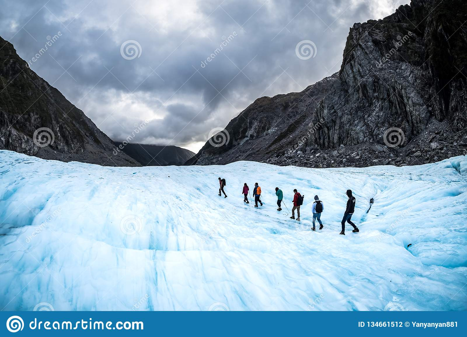 Hikers and travelers walking on ice in Fox Glacier, New Zealand
