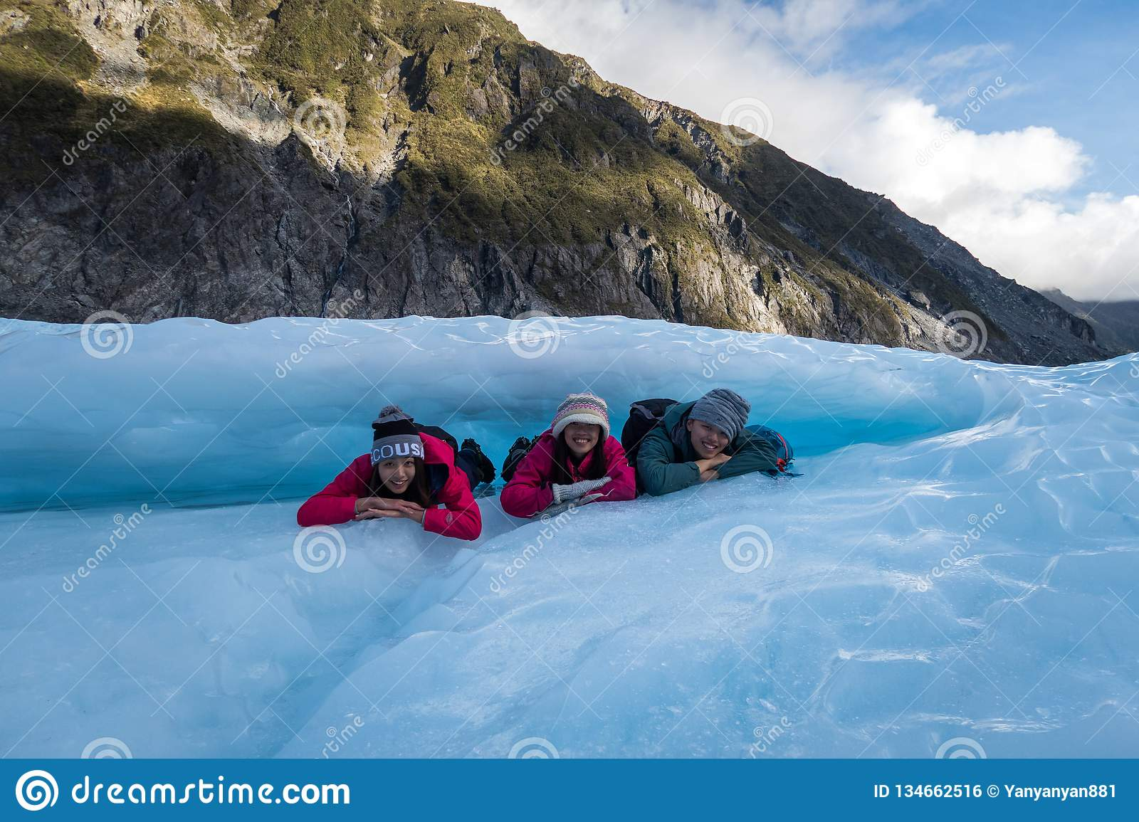 Group of travellers laying under a ice arch at Fox Glacier in New Zealand