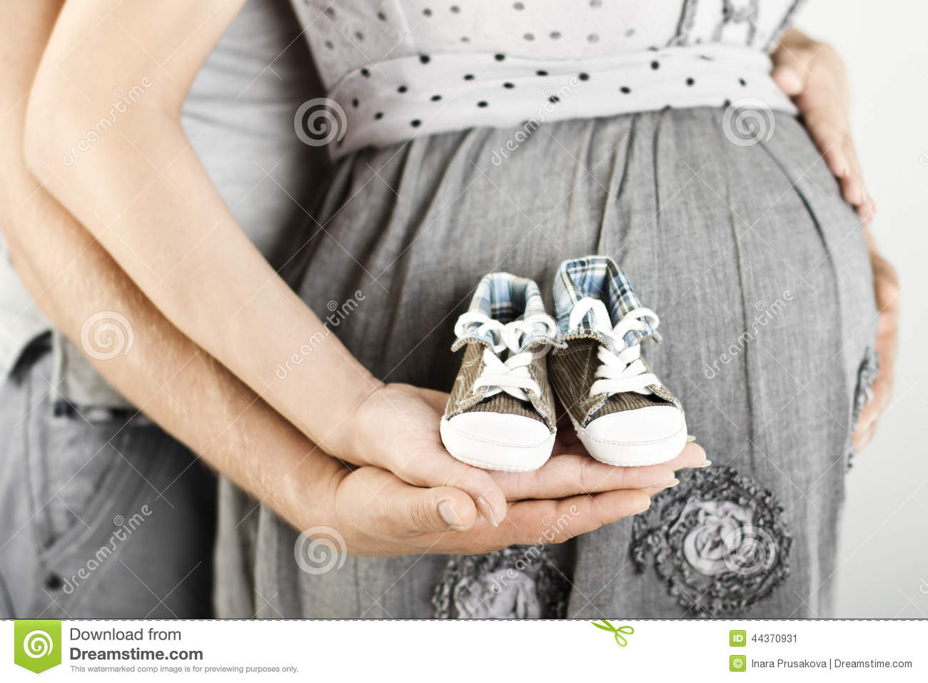 Newborn baby booties in parents hands, Pregnant woman belly