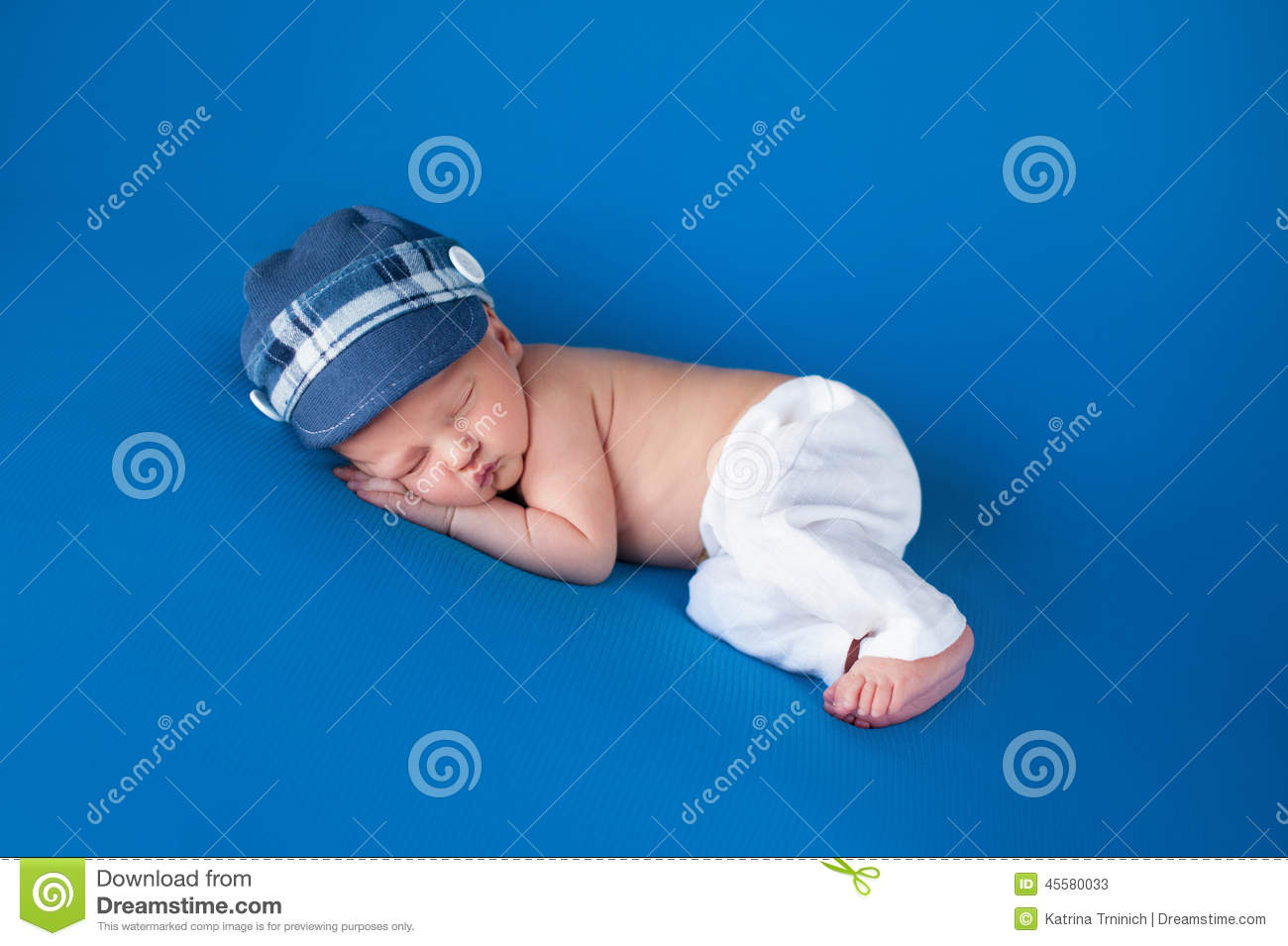 Portrait of an eight day old newborn baby boy. He is sleeping on his side  wearing a blue newsboy   golf cap and white linen pants. bc118e9a721