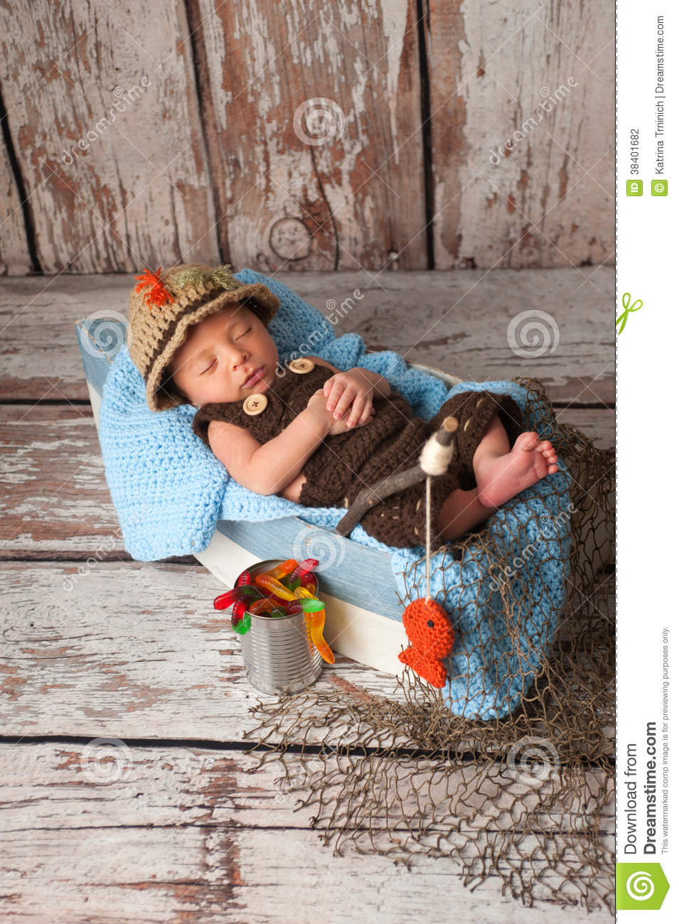 Portrait of a nine day old newborn baby boy. He is sleeping in a miniature  boat and wearing crocheted overalls and a fisherman s hat. 4305e4bf439f