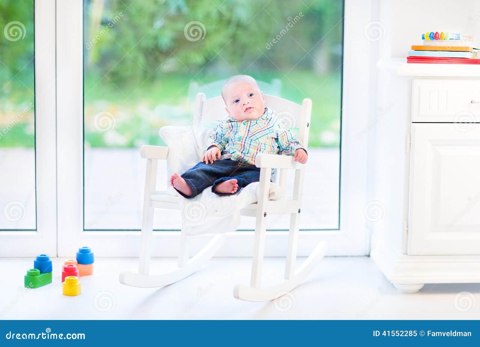 Newborn baby boy in rocking chair next window stock photo for Chair next to window