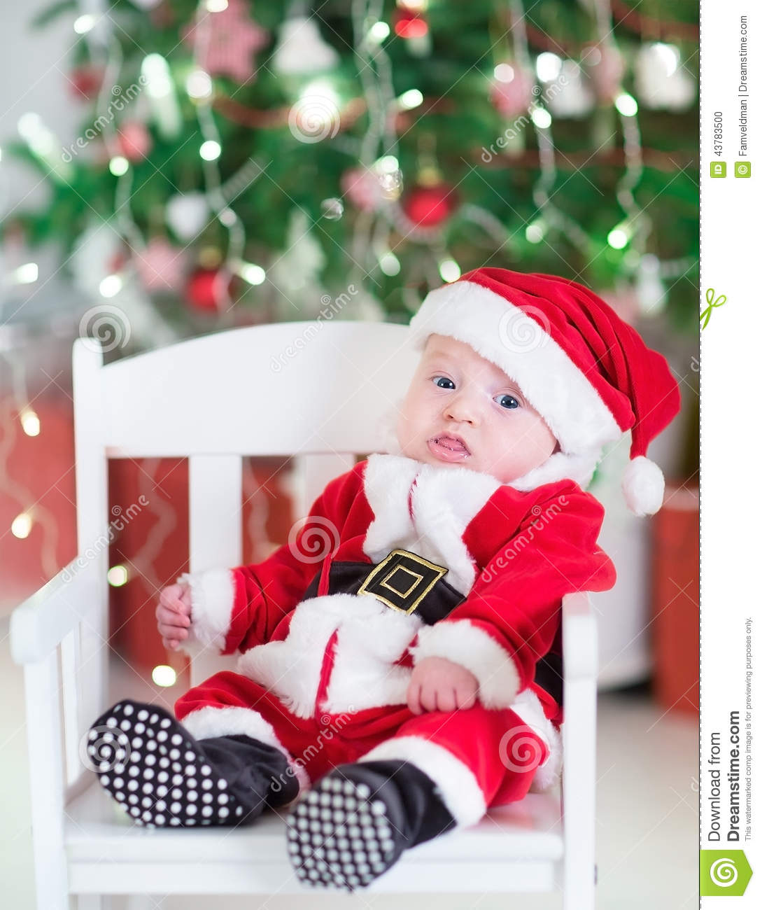 Newborn baby boy in Santa outfit sitting under Chr