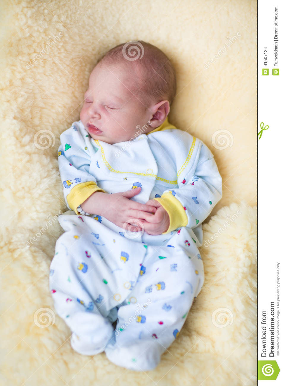 Newborn Baby Boy Sleeping On A Sheepskin Stock Photo