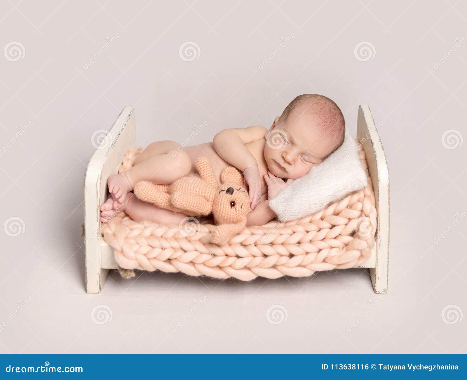 Newborn baby boy sleeping on a small bed