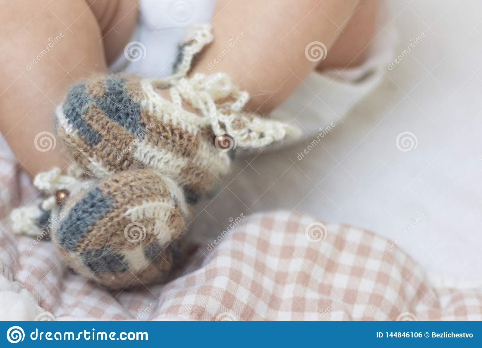 Newborn baby feet close up in wool brown knitted socks booties on a white blanket. The baby is in the crib