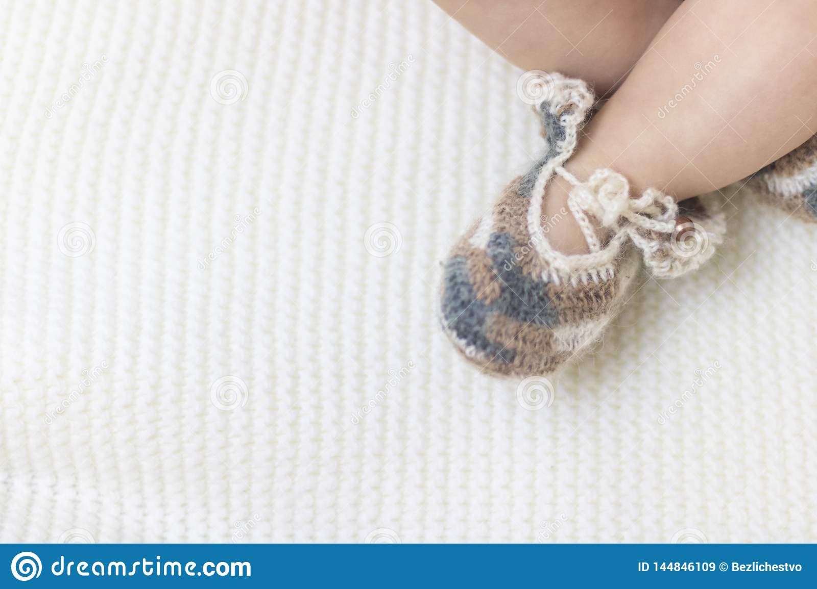 Newborn baby feet close up in wool brown knitted socks booties on a white blanket. The baby is in the crib. In the right corner.