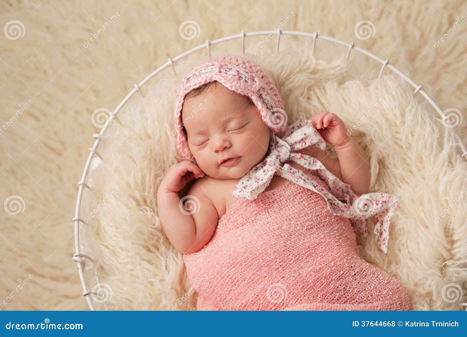 Newborn Baby Girl In Basket Wearing A Pink Bonnet Stock