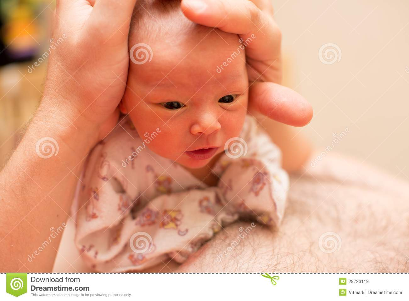 Newborn baby girl on the fathers hands at home. Use it for a child