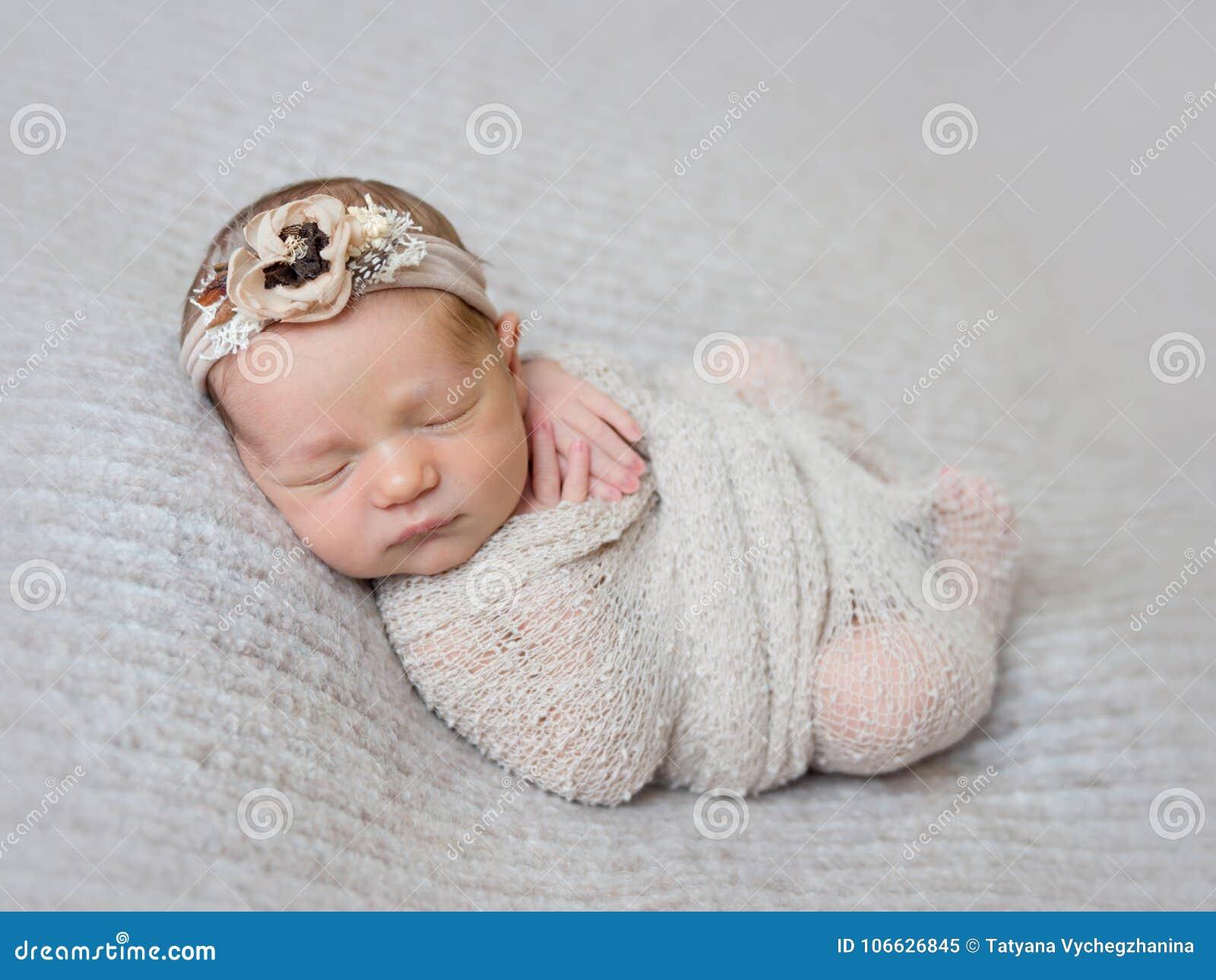 02c0efcb7 Newborn baby girl with flower headband on her little head swaddled in beige  wrap.