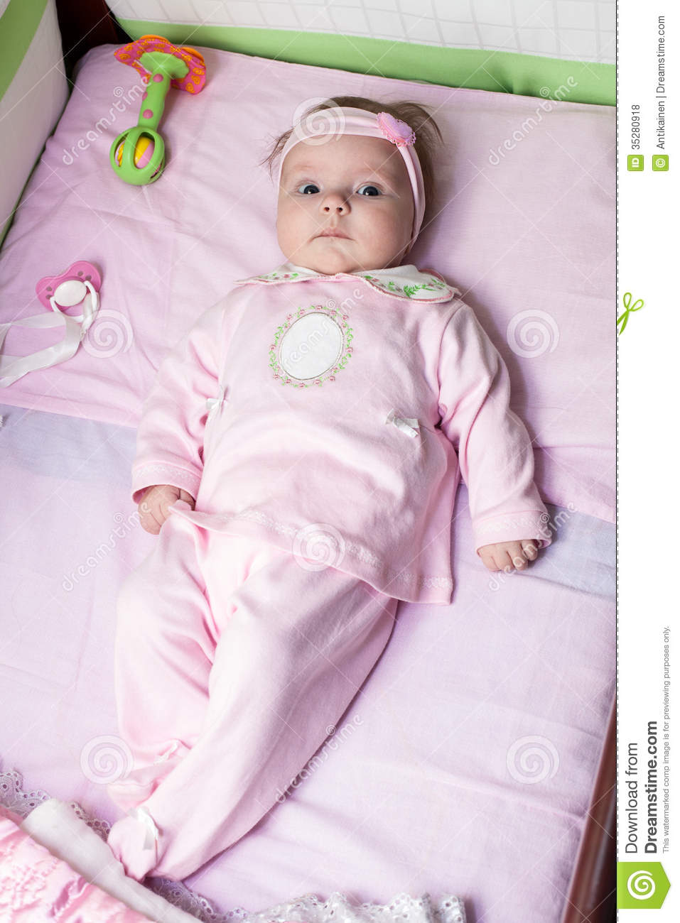 Newborn baby girl is laying in bed