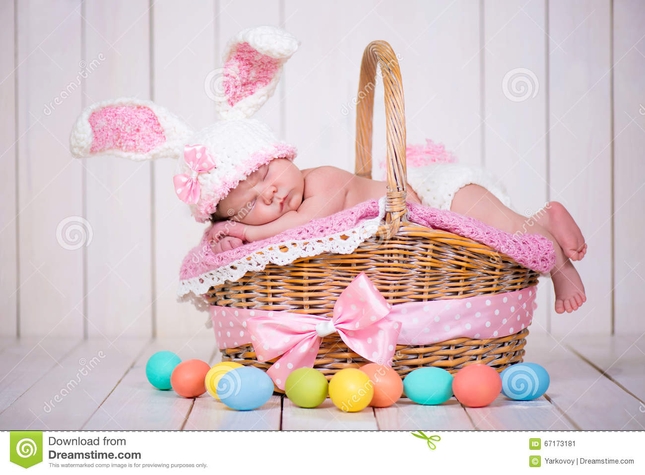 Newborn baby girl in a rabbit costume has sweet dreams on the wicker royalty free stock photo negle Image collections