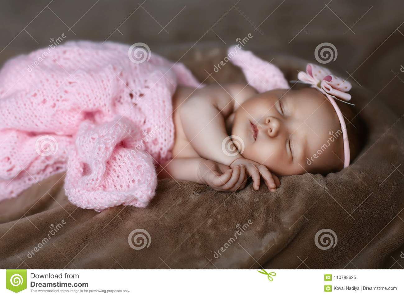 Newborn baby girl sleeping cute, covered with soft pink scarf, neatly folded under a pen with a small head with a pink bow, set