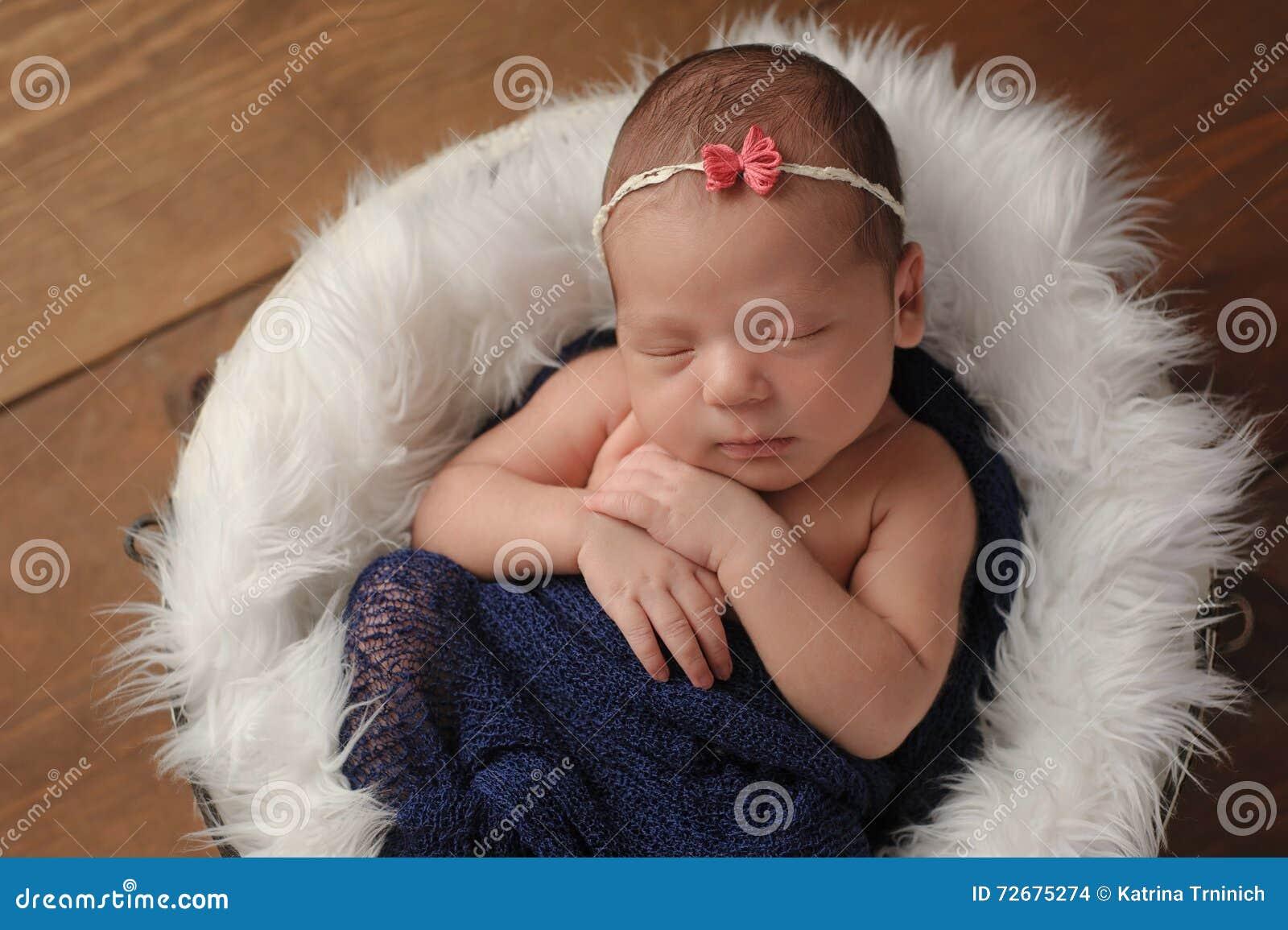 Newborn Baby Girl Sleeping in Fur Lined Bucket