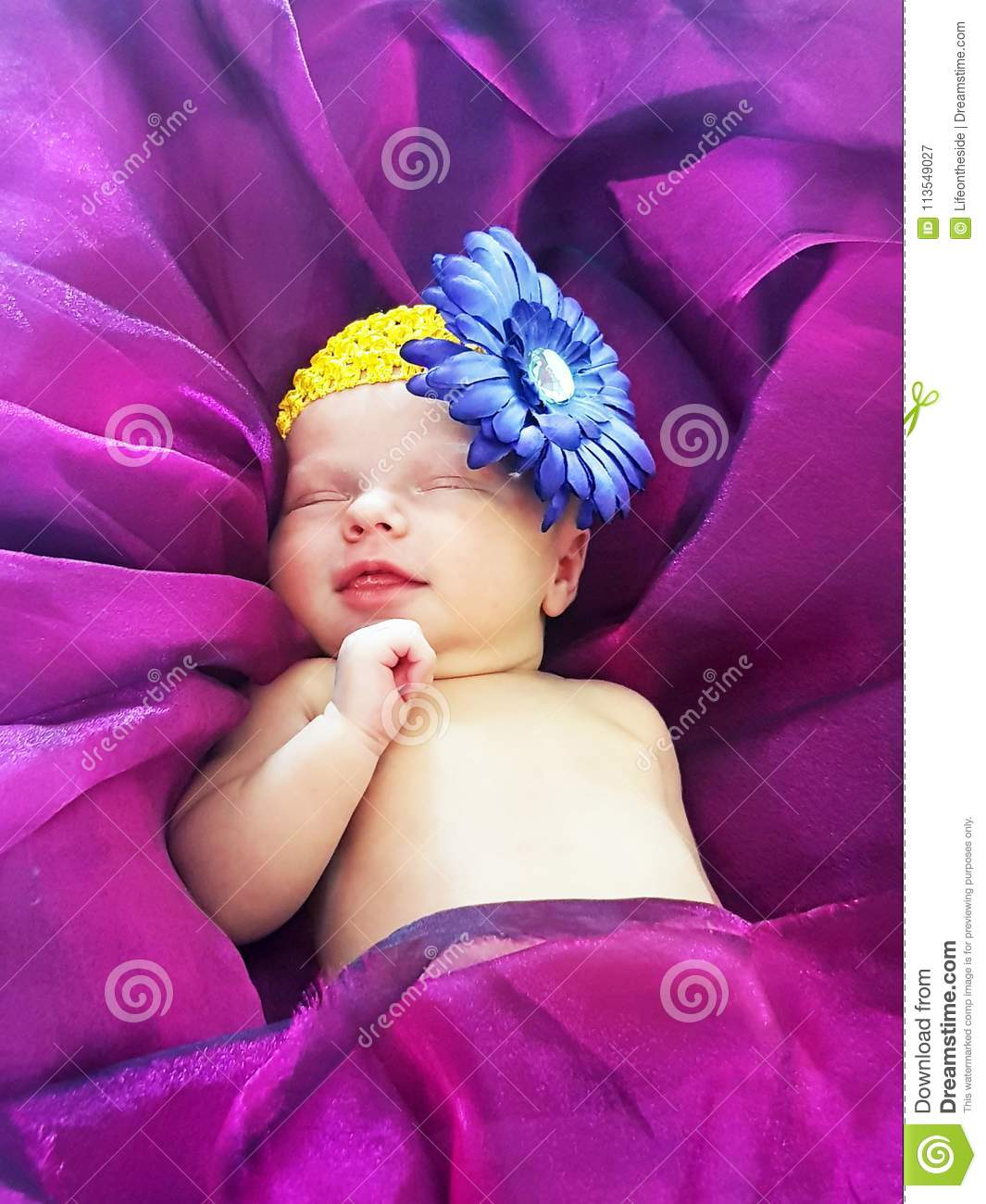 Newborn baby girl smiling sleeping on bed ultra violet purple