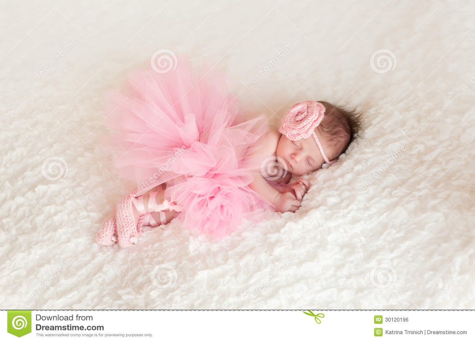 2e9aa628ec Newborn baby girl wearing a pink crocheted headband, ballerina tutu, and ballet  slippers. She is sleeping on white billowy fabric.