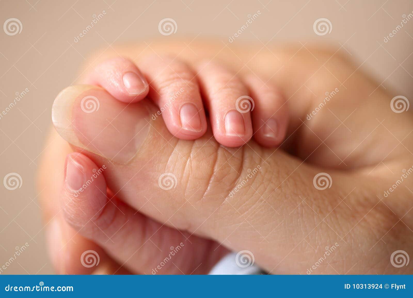 Newborn baby grasps his mother s hand