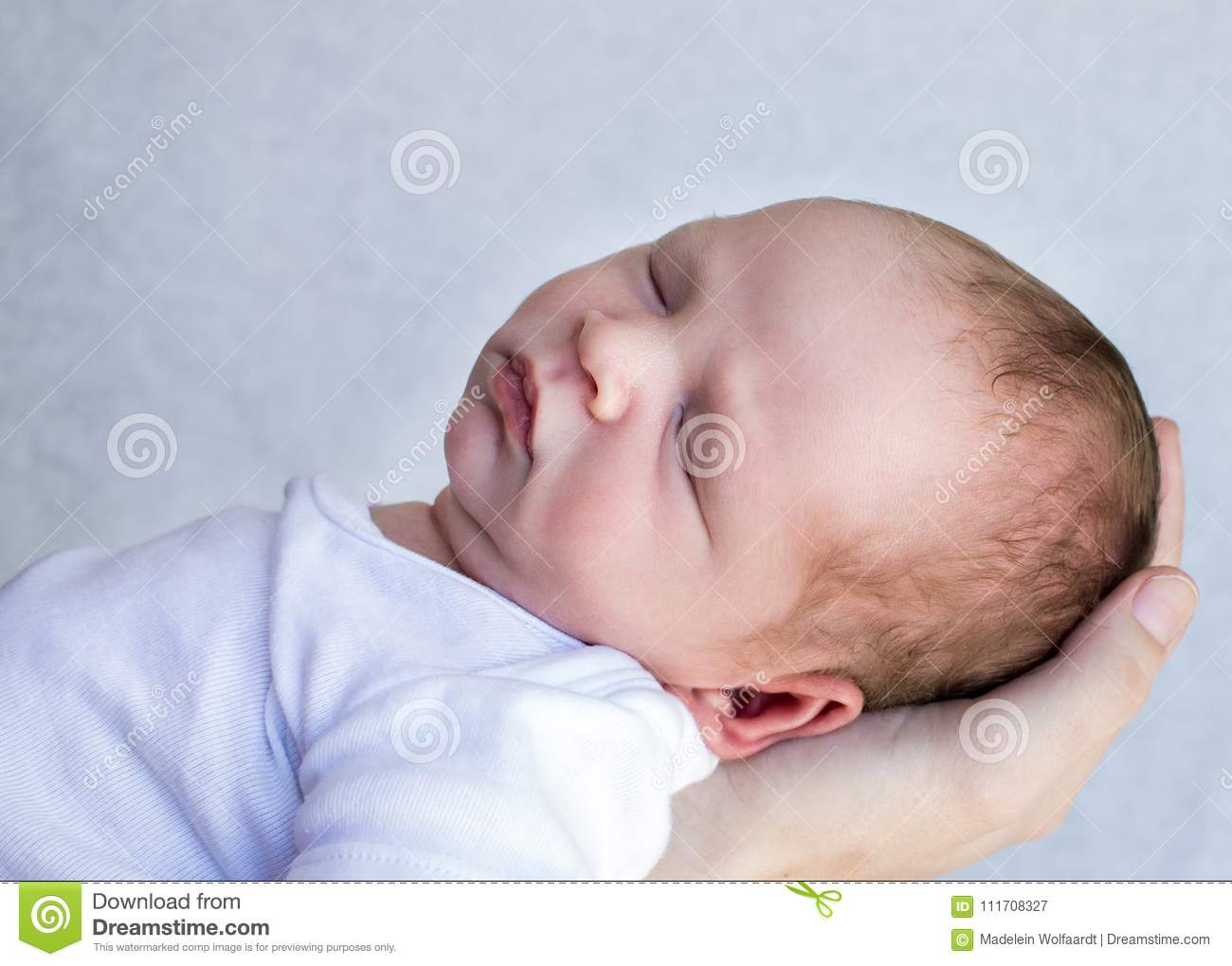 Newborn baby sleeping closeup of his face with a person`s hand